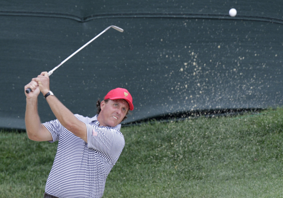 Photo - United States'  Phil Mickelson hits from the sand on the first hole during a foursome match against the International team at the Presidents Cup golf tournament at Muirfield Village Golf Club Friday, Oct. 4, 2013, in Dublin, Ohio. (AP Photo/Jay LaPrete)