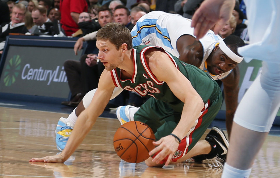 Photo - Milwaukee Bucks guard Luke Ridnour, front, picks up loose ball as Denver Nuggets guard Ty Lawson covers in the first quarter of an NBA basketball game in Denver, Wednesday, Feb. 5, 2014. (AP Photo/David Zalubowski)