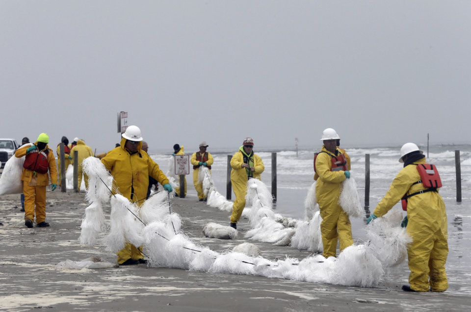 Photo - A crew spreads a viscous snare along East Beach to trap oil Monday, March 24, 2014, in Galveston, Texas.  Thousands  of gallons of tar-like oil spilled into the major U.S. shipping channel after a barge ran into a ship Saturday. (AP Photo/Pat Sullivan)