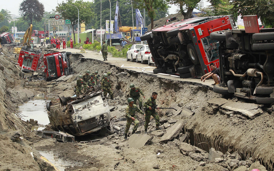 Photo - Soldiers use electronic sensors to search for missing persons believed to be buried after massive gas explosions in Kaohsiung, Taiwan, Friday, Aug. 1, 2014. A series of explosions about midnight Thursday and early Friday ripped through Taiwan's second-largest city, killing scores of people, Taiwan's National Fire Agency said Friday. (AP Photo/Wally Santana)