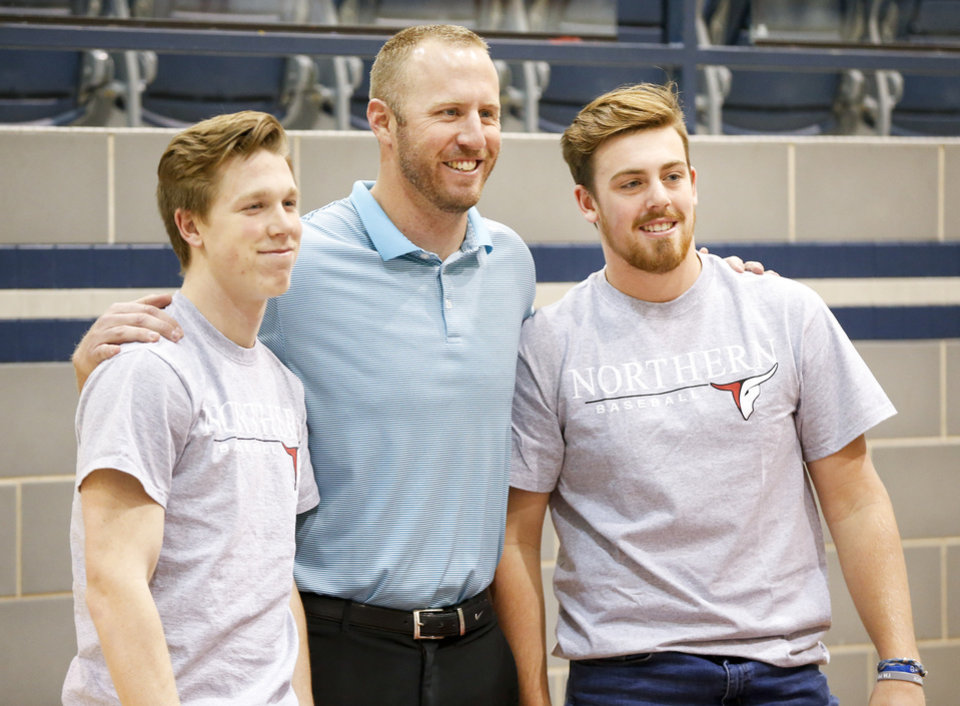 Photo - Edmond North baseball coach Grant Ledbetter, middle, poses for a photo with Ben MacNaughton, left, and Garrett Crone before a ceremony for National Signing Day at Edmond North High School in Edmond, Okla., Wednesday, Feb. 7, 2018. MacNaughton and Crone signed to play baseball at Northern Oklahoma College. Photo by Nate Billings, The Oklahoman