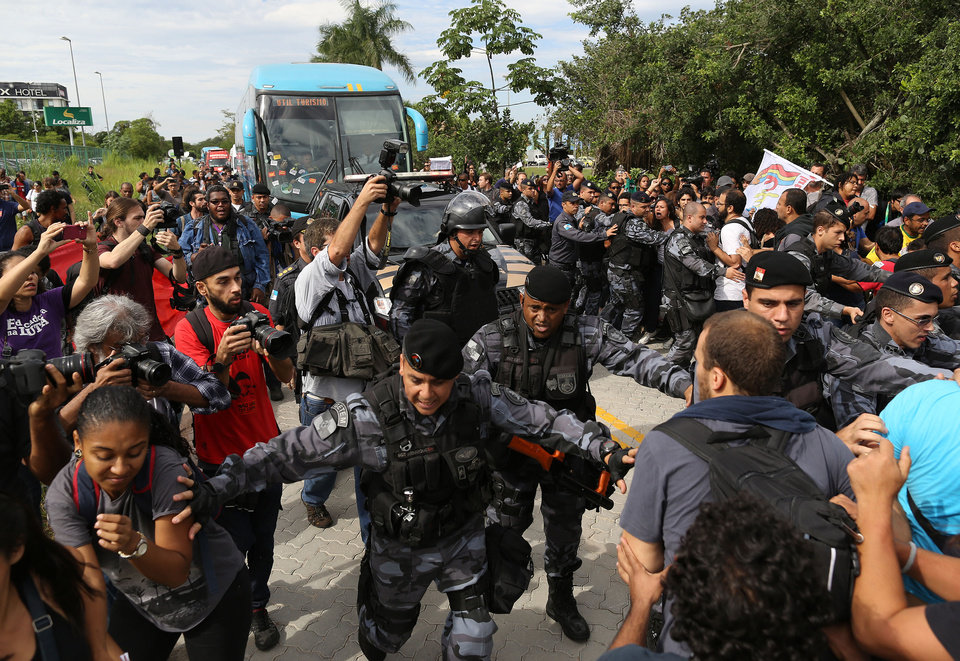 Photo - Riot police try to keep demonstrators away from the bus carrying some members of Brazil's national soccer team departing for the Granja Comary training center, where the team will stay during the World Cup, in Rio de Janeiro, Brazil, Monday, May 26, 2014. Demonstrators are protesting against the money being spent by the local government on the World Cup.  (AP Photo/Leo Correa)