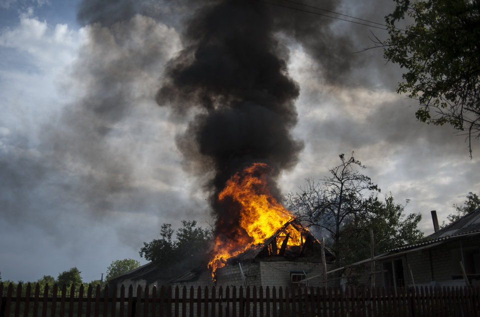 Photo - A private house burns after it was set on fire by a mortar shell, on the outskirts of the town of Lysychansk, Ukraine, on Thursday, May 22, 2014. In the eastern Luhansk region, sustained gunfire and shelling rocked the town of Lysychansk. One mortar bomb hit a house, which burst into flames. Earlier today at least 11 Ukrainian troops were killed and about 30 others were wounded during an attack at a military checkpoint, the deadliest raid in the weeks of fighting in eastern Ukraine. (AP Photo/Evgeniy Maloletka)