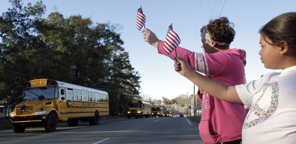 Photo - Kiya Buchanan, right, and Raechel Buchanan, left, hold up flags as the funeral procession for Charles Albert Poland Jr., passes by on Sunday, Feb. 3, 2013, in Ozark, Ala. (AP Photo/Butch Dill)