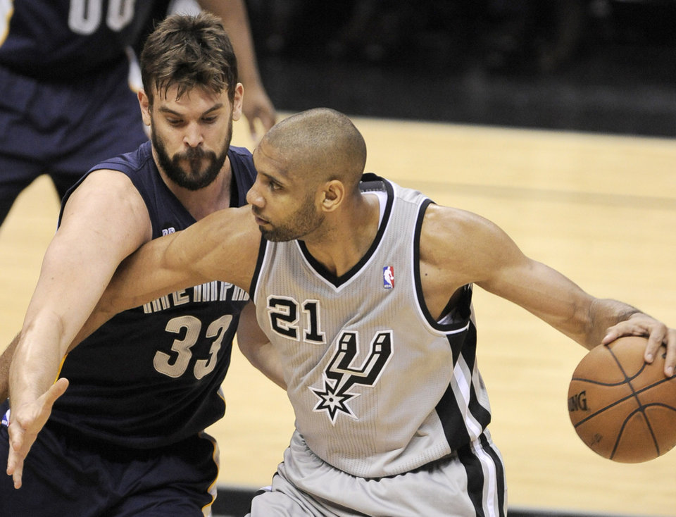 Photo - Memphis Grizzlies' Marc Gasol, left, of Spain, defends against San Antonio Spurs' Tim Duncan during the first half of Game 1 of the Western Conference final NBA basketball playoff series on Sunday, May 19, 2013, in San Antonio. (AP Photo/Darren Abate)