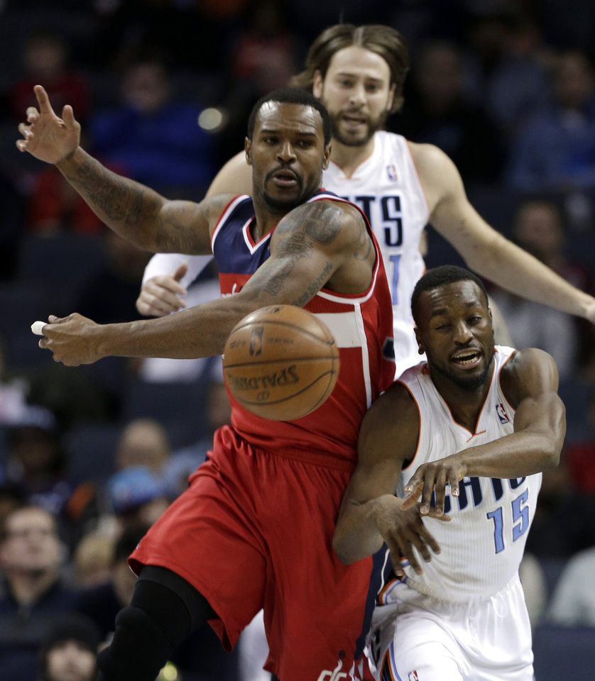 Photo - Charlotte Bobcats' Kemba Walker, right, and Washington Wizards' Trevor Booker, left, chase a loose ball as Charlotte's Josh McRoberts, back, looks on watches during the first half of an NBA basketball game in Charlotte, N.C., Tuesday, Jan. 7, 2014. (AP Photo/Chuck Burton)