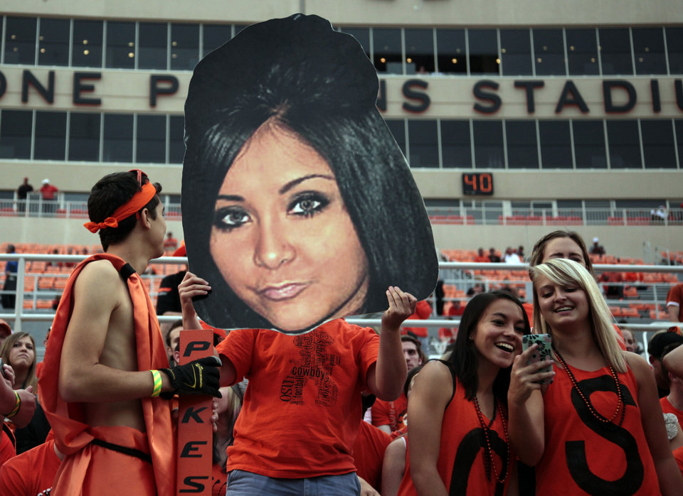 Photo - Nick Isburgh holds up a giant Snooki face before the college football game between Oklahoma State University (OSU) and the University of Texas (UT) at Boone Pickens Stadium in Stillwater, Okla., Saturday, Sept. 29, 2012. Photo by Sarah Phipps, The Oklahoman