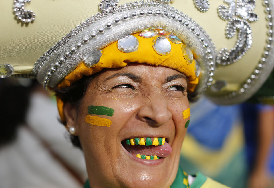 Photo - A Brazil soccer fan with her teeth decorated in the colors of her soccer team poses for a photo before watching the World Cup semifinal match between Brazil and Germany on a live telecast inside the FIFA Fan Fest area on Copacabana beach in Rio de Janeiro, Brazil, Tuesday, July 8, 2014. (AP Photo/Leo Correa)