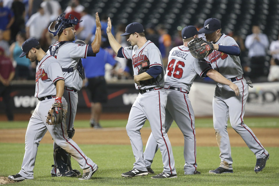Photo - The Atlanta Braves celebrate their 3-2 win over the New York Mets after the ninth inning of their baseball game, Wednesday, Aug. 27, 2014, in New York. (AP Photo/John Minchillo)