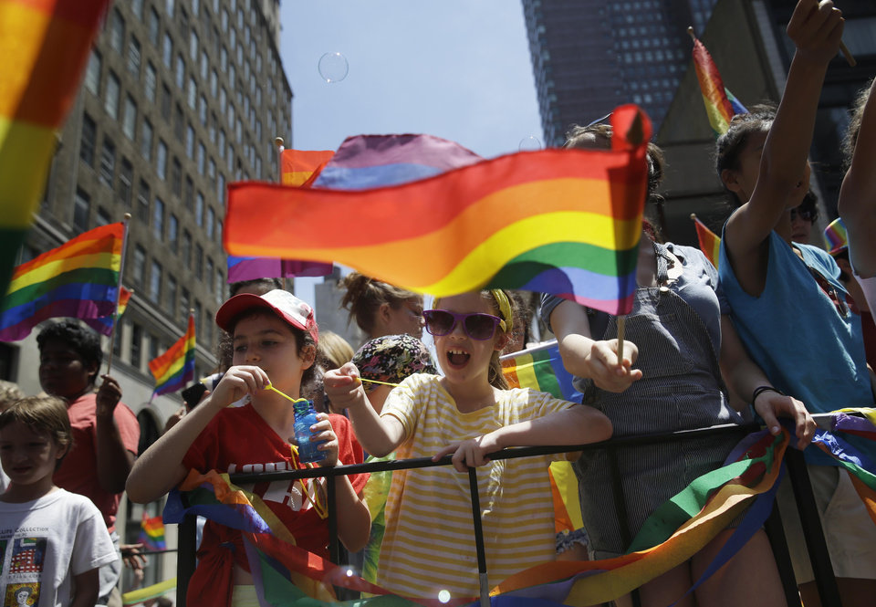 Photo - Children blow bubbles as they pass by on a float in the Gay Pride Parade in New York, Sunday, June 29, 2014. Fifth Avenue became one big rainbow on Sunday, as thousands of participants waving multicolored flags made their way down the street for New York City's annual Gay Pride march. (AP Photo/Seth Wenig)