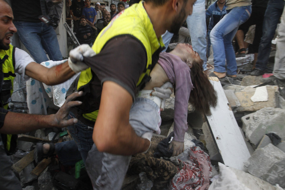 Photo -   An emergency rescue worker carries a child's body found in the Daloo family house rubble following an Israeli airstrike in Gaza City, Sunday, Nov. 18, 2012. Palestinian medical officials say at least 10 civilians, including women and young children, have been killed in an Israeli airstrike in Gaza City. (AP Photo/Hatem Moussa)
