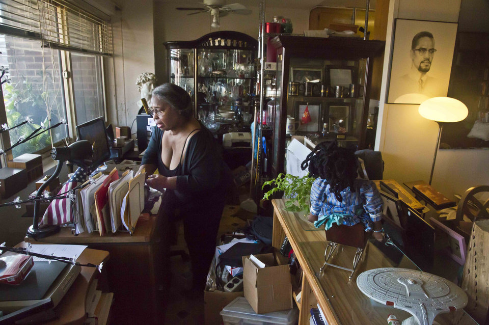 Photo - In this Aug. 5, 2014 photo, Jean Green Dorsey, a rent-stabilized tenant in a building on New York City's Upper West Side, looks for documents on her desk.  Dorsey and her late husband, astronomer, Dr. William Dorsey, moved to the apartment in 1972. Although she has been in the building in excess of 40 years, Dorsey is unable to avail herself of some of its amenities that market residents enjoy. (AP Photo/Bebeto Matthews)