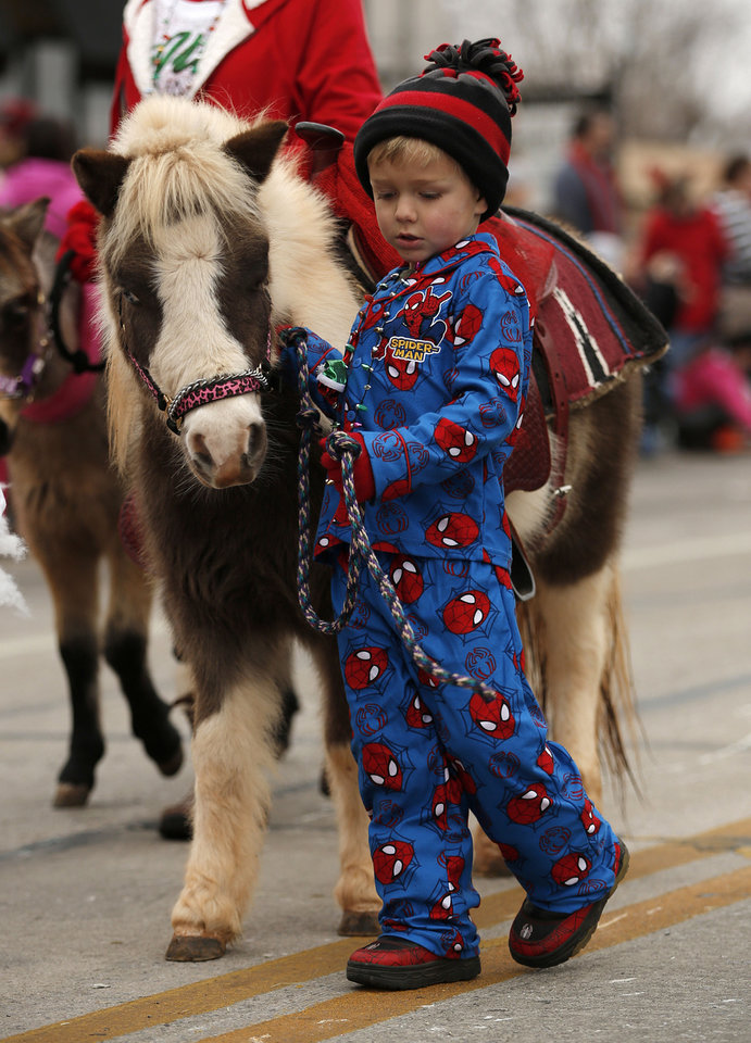 Lane Moring, 5, walks with a horse in the parade.