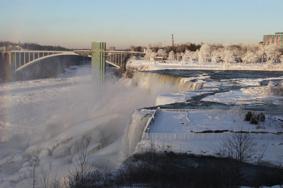 Photo - The area surrounding Niagara Falls is coated in a layer of ice in Niagara Falls State Park, Niagara Falls, N.Y. on Thursday, Jan. 9, 2014.  Niagara Falls hasn't frozen over, but it has become an icy spectacle, thanks to a blast of arctic wind and cold that blew around and froze the mist on surfaces and landscaping. Despite the urban legends, Niagara Falls doesn't freeze solid in the winter, tourism officials say.  A section of the American Falls, one of three waterfalls that make up the natural attraction, has frozen. The Niagara River rapids and larger Horseshoe Falls continue to flow unimpeded. (AP Photo/The Buffalo News, Sharon Cantillon)  MANDATORY CREDIT