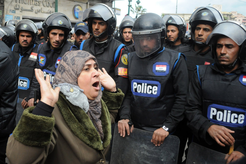 Photo - A woman reacts as she stands before riot policemen separating opponents of Egyptian President Mohammed Morsi clashing with Islamist supporters of the president in Alexandria, Egypt, Friday, Dec. 21, 2012. Thousands of Islamists clashed with their opponents Friday in Egypt's second largest city, Alexandria, on the eve of the second leg of voting on the country's contentious constitution that has deeply polarized the nation.(AP Photo)