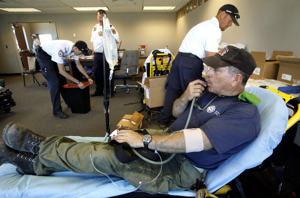 Photo - Newalla firefighter Chris Peeples is re-hydrated Friday in a rehab room. Peeples was one of three Newalla firefighters sent Friday to help Luther firefighters with a large wildfire. Photos by Jim Beckel, The Oklahoman