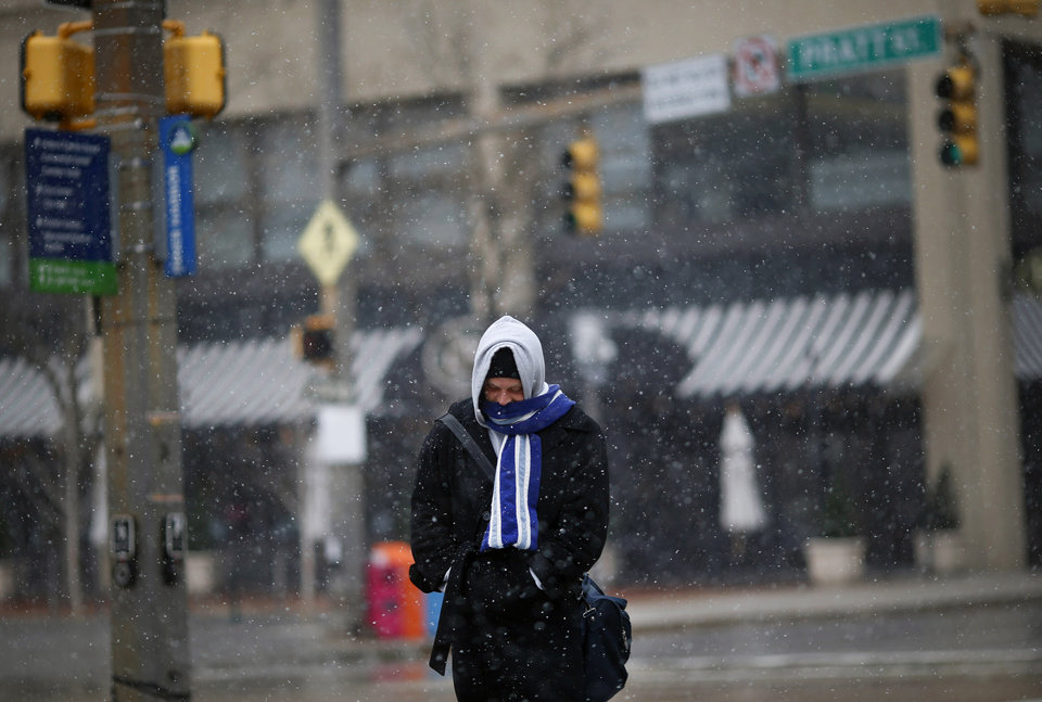 Photo - A man stays bundled up as he walks through a light snowfall in Baltimore, Tuesday, March 25, 2014. An unwelcome nor'easter is expected in the region just days after the start of spring. (AP Photo/Patrick Semansky)