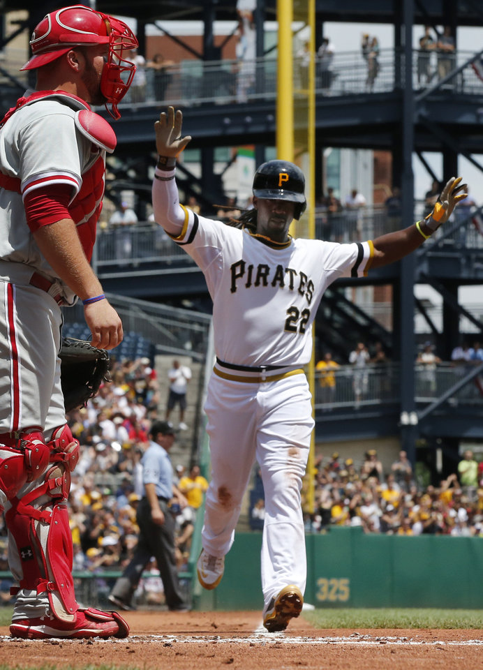 Photo - Pittsburgh Pirates' Andrew McCutchen,right,  scores on a double by Pirates' Russell Martin off Philadelphia Phillies starting pitcher A.J. Burnett in the first inning of a baseball game against the Pittsburgh Pirates in Pittsburgh Sunday, July 6, 2014. At left is Philadelphia Phillies catcher Cameron Rupp. (AP Photo/Gene J. Puskar)