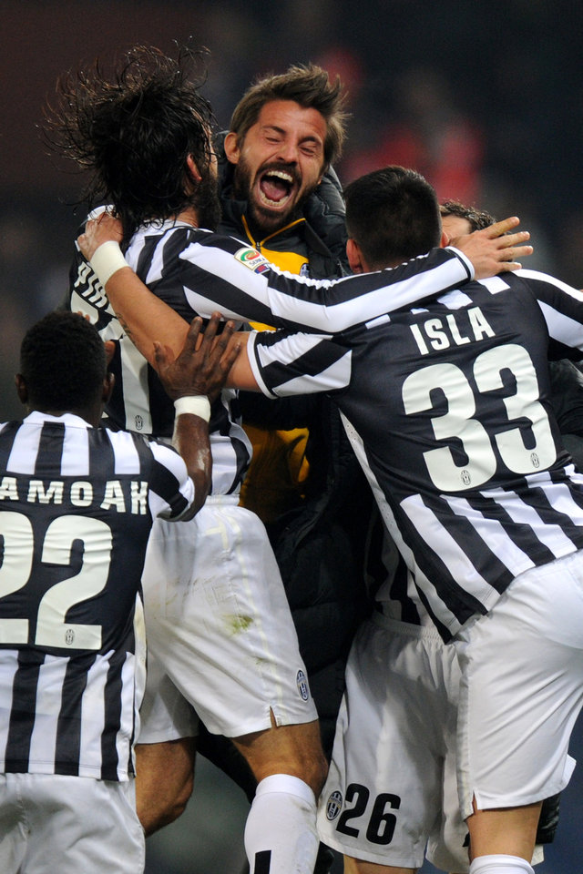 Photo - Juventus' Andrea Pirlo, second left, celebrates with teammates after scoring during a Serie A soccer match between Genoa and Juventus, at Genoa's Luigi Ferraris Stadium, Italy, Sunday, March 16, 2014. A late Andrea Pirlo goal saw Juventus maintain its charge to a third successive Serie A title as it beat Genoa 1-0 on Sunday to extend its lead to 17 points. Pirlo fired home a stunning free kick two minutes from time as Juventus struggled to a victory after Gianluigi Buffon had saved Emanuele Calaio's penalty for Genoa. (AP Photo/Tano Pecoraro)