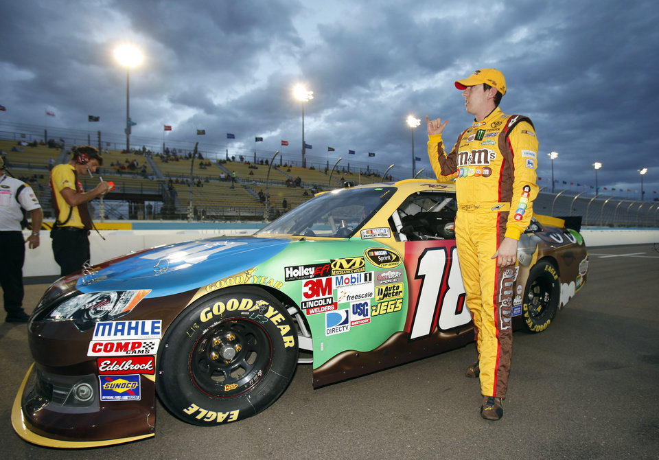 Photo -   Kyle Busch gestures to cheering fans after winning the pole during qualifying for Sunday's NASCAR Sprint Cup Series auto race, Friday, Nov. 9, 2012, at Phoenix International Raceway in Avondale, Ariz. (AP Photo/Paul Connors)