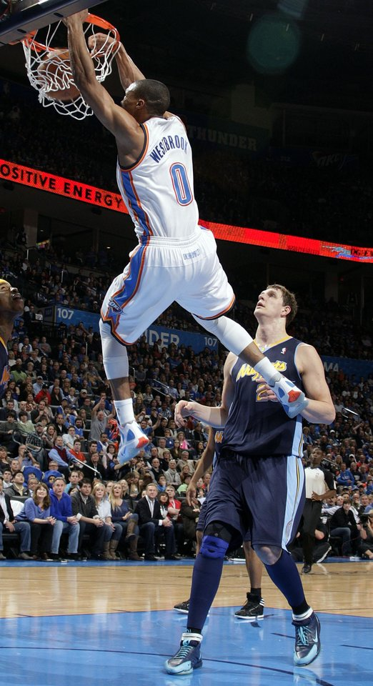 Photo - Oklahoma City's Russell Westbrook (0) dunks in front of Denver's Timofey Mozgov (25) during the NBA basketball game between the Oklahoma City Thunder and the Denver Nuggets at the Chesapeake Energy Arena, Sunday, Feb. 19, 2012. Photo by Sarah Phipps, The Oklahoman