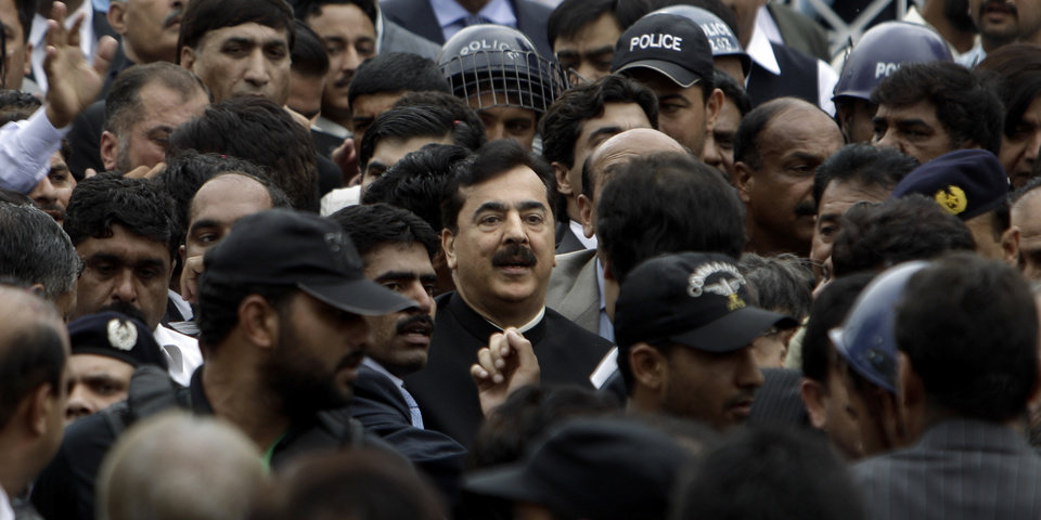 Photo -   Pakistani Prime Minister Yousuf Raza Gilani, center, surrounded by guards, leaves the Supreme court following a hearing in Islamabad, Pakistan, Thursday, April 26, 2012. The Supreme Court convicted Gilani of contempt on Thursday for refusing to reopen an old corruption case against President Asif Ali Zardari, but spared him a prison term in a case that has stoked political tensions in the country. (AP Photo/Muhammed Muheisen)