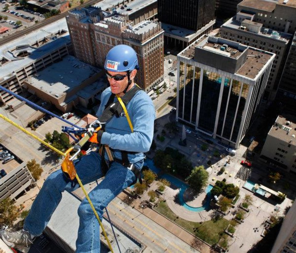 David Zizzo descends the south side of  SandRidge Building as he rappels from the top of the building in downtown Oklahoma City Wednesday, Oct. 13, 2010.   Photo by Jim Beckel