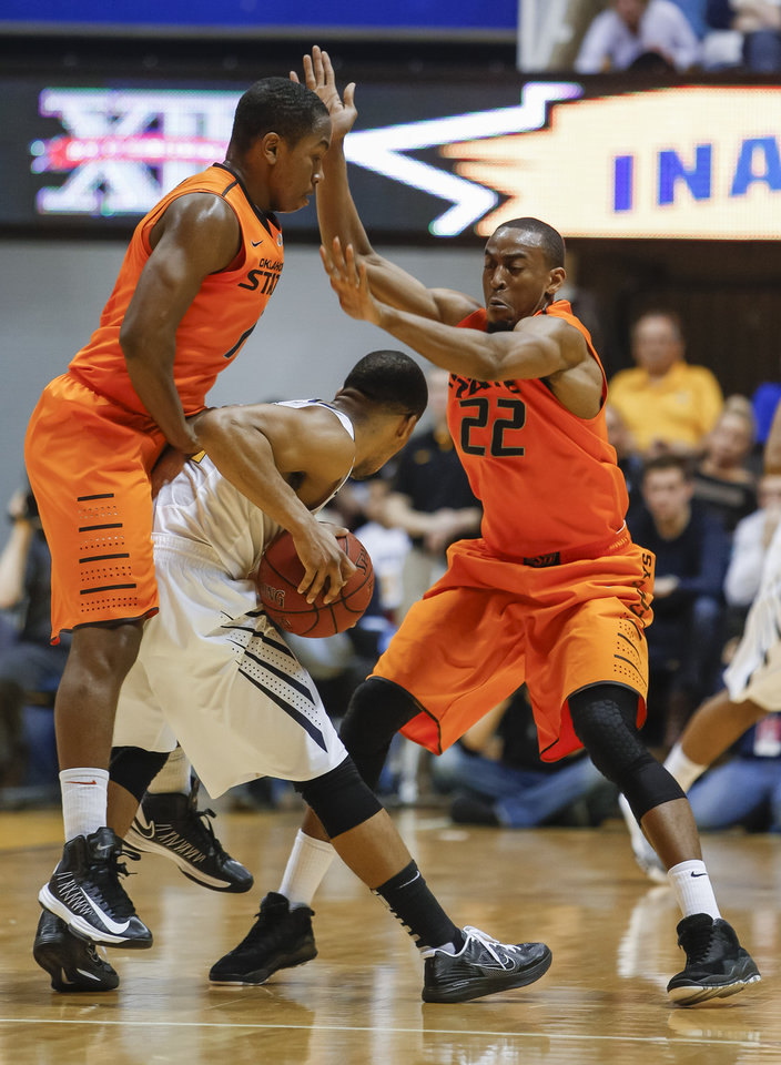 Photo - Oklahoma State's  Jean-Paul Olukemi, left, and Markel Brown (22) defend West Virginia's Gary Browne, center, during the first half of an NCAA college basketball game in Morgantown, W.Va., on Saturday, Feb. 23, 2013. (AP Photo/David Smith)