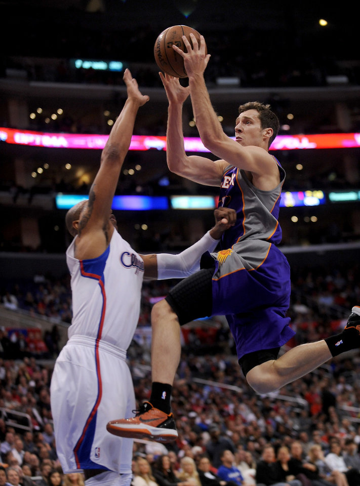 Photo - Los Angeles Clippers forward Caron Butler, left, defends as Phoenix Suns guard Goran Drapic, right, of Slovenia, drives to the basket in the first half of an NBA basketball game in Los Angeles on Wednesday, April  3, 2013. (AP Photo/Richard Hartog)