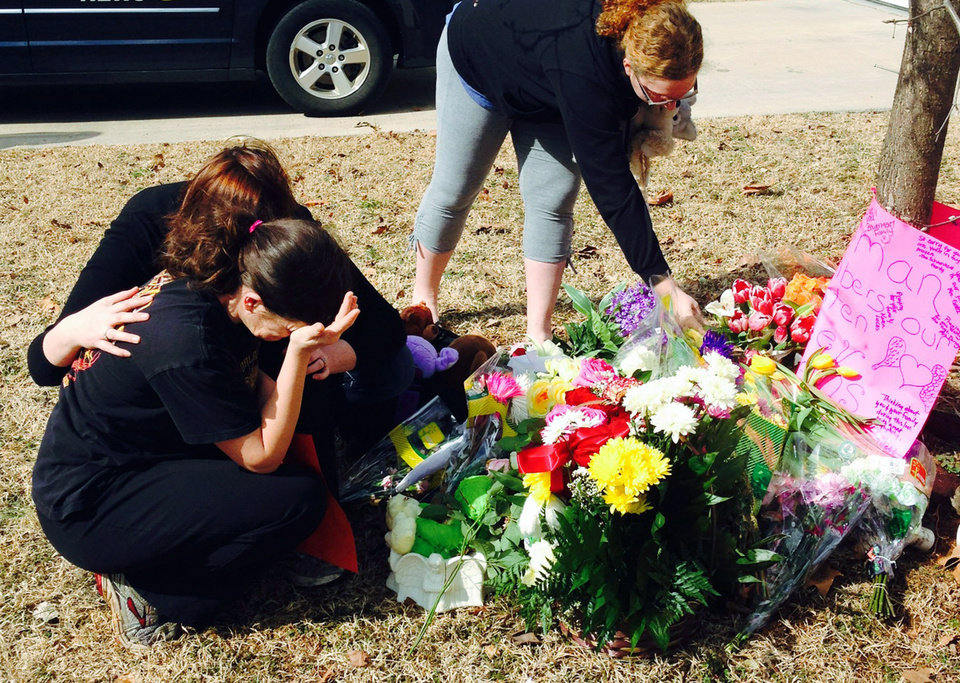 Photo - CORRECTS LAST NAME OF VICTIM'S MOTHER TO BARFIELD INSTEAD OF OWENS - Stacey Barfield, mother of Hailey Owens, foreground left, is consoled by Sara Wells, as family member Teri Nord, right, arranges flowers left by well wishers Thursday, Feb. 20, 2014 near the site where the 10-year-old girl was abducted just blocks from her Springfield, Mo., home. Prosecutors have charged Craig Michael Wood with first-degree murder, kidnapping and armed criminal action in their girls death. Prosecutors says the fourth-grader's body was found stuffed in two trash bags inside plastic storage containers in the basement of Wood's Springfield home. She had been shot in the head. (AP Photo/Alan Scher Zagier)