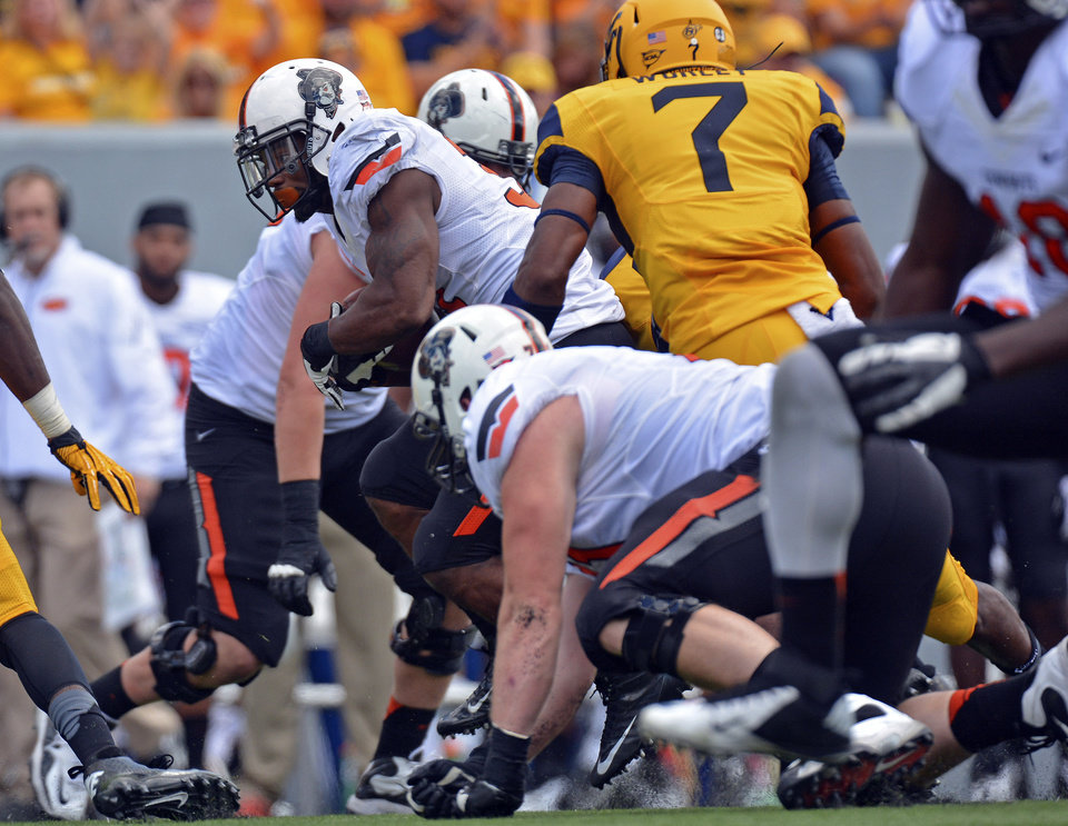 Photo - Oklahoma State running back Jeremy Smith (31) drags the West Virginia defense during the fourth quarter of an NCAA college football game in Morgantown, W.Va., on Saturday, Sept. 28, 2013. (AP Photo/Tyler Evert) ORG XMIT: WVTE107