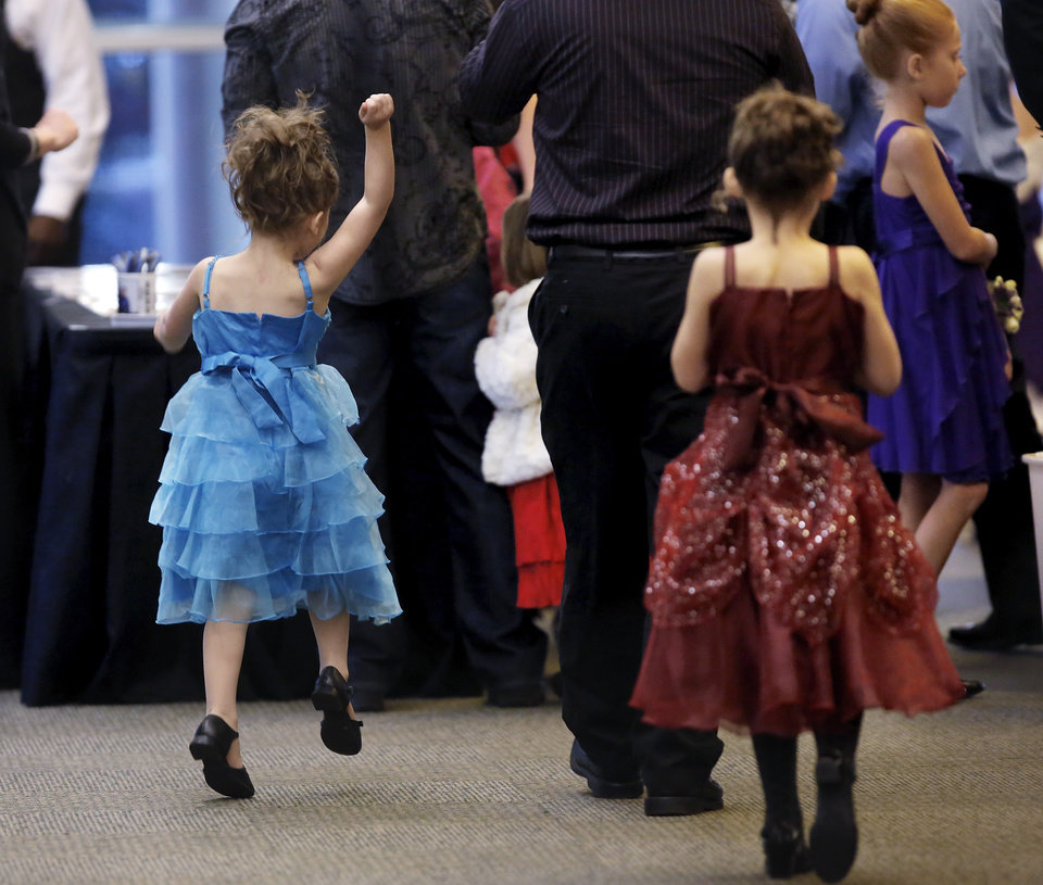 An  girl skips excitedly in the direction of a group of her friends. Midwest City Parks and Recreation Department hosted the city's annual Daddy-Daughter Dance that featured three 90-minute dance sessions at the Reed Center on Saturday, Feb. 16, 2013.    Photo by Jim Beckel, The Oklahoman