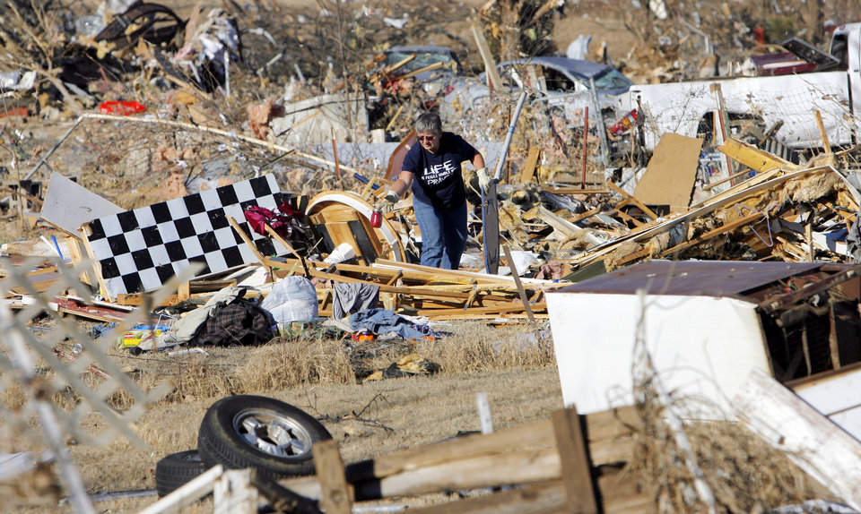 Photo - Tammie Rose searches for items to salvage from the destroyed mobile home in which her daughter, Shawna Inlow, used to live in Lone Grove, Okla., Wednesday, February 11, 2009. On Tuesday, February 10, 2009, a tornado moved through Lone Grove killing at least eight people. Inlow and her three boys were able to ride  out the storm safely in Rose's cellar. BY NATE BILLINGS, THE OKLAHOMAN