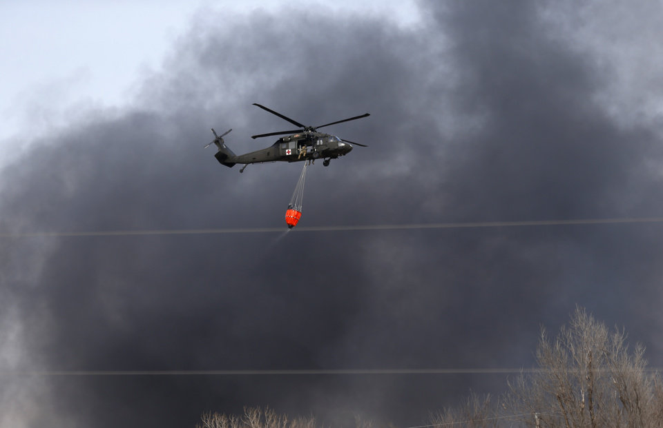 Photo - An helicopter prepares to drop water on a wildfire near SE 164th and Air Depot builds in southeast Oklahoma City, Okla., Sunday, Feb. 12, 2017. Photo by Sarah Phipps, The Oklahoman