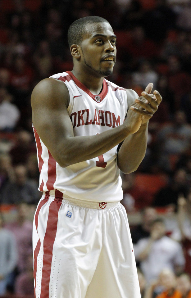 Photo - Sooner's Sam Grooms (1) applauds a play during the second half as the University of Oklahoma Sooners (OU) defeat  the Oklahoma State Cowboys (OSU) 77-68  in NCAA, men's college basketball at The Lloyd Noble Center on Saturday, Jan. 12, 2013  in Norman, Okla. Photo by Steve Sisney, The Oklahoman