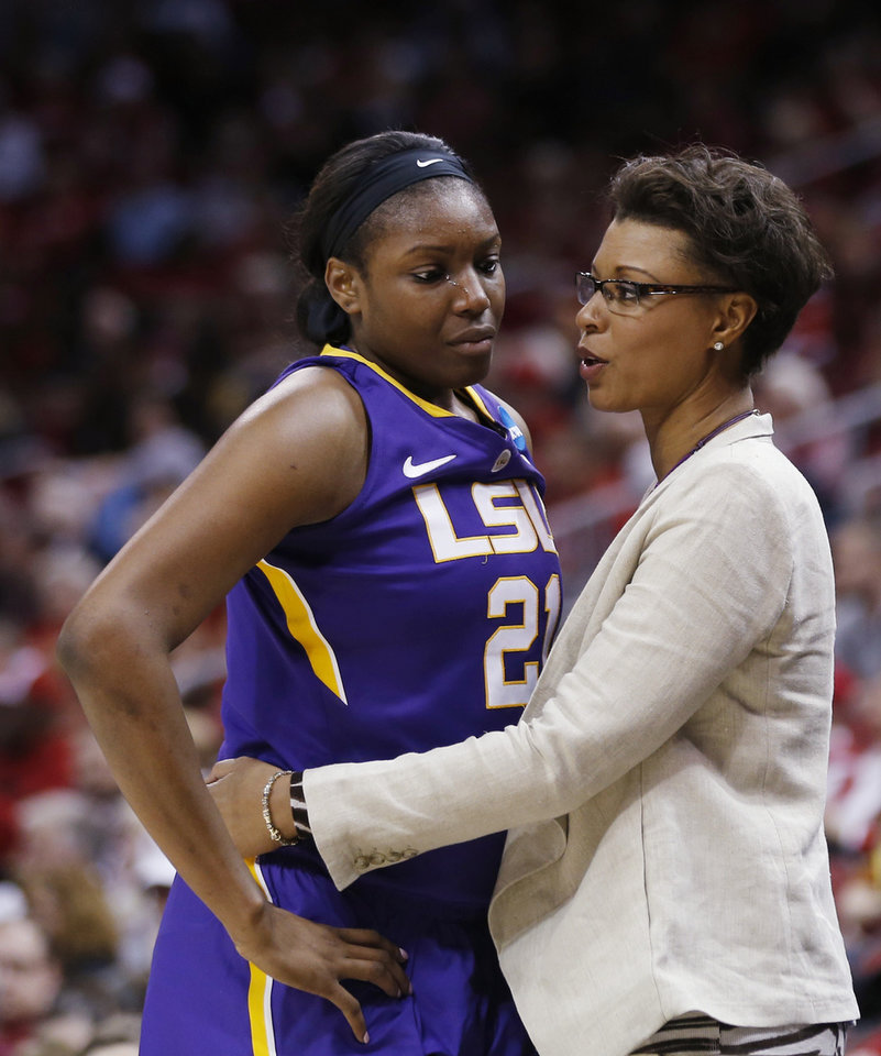 Photo - LSU head coach Nikki Caldwell embraces LSU forward Shanece McKinney (21) in the final moments of their 73-47 loss to Louisville in a regional semi final game at the NCAA college basketball tournament, Sunday, March 30, 2014, in Louisville, Ky. (AP Photo/John Bazemore)