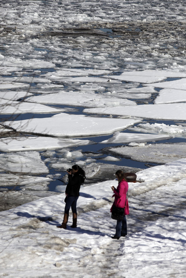 Photo - Visitors take pictures of an ice filled Chicago River Wednesday, Feb. 19, 2014, in downtown Chicago. Weeks of subfreezing weather are giving way, at least briefly, to temperatures in the 50s, putting cities on guard for flooding, roof collapses and clogged storm drains. (AP Photo/Kiichiro Sato)