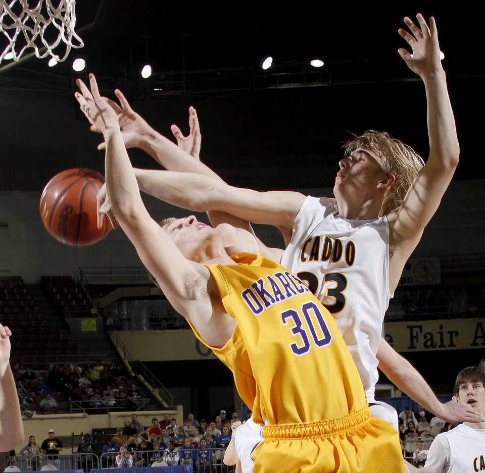 Photo - Caddo's Clayton Childree, right, defends Okarche's Ryan Raupe during the Class A boys basketball state tournament at the State Fair Arena in Oklahoma City, Friday, March 5, 2010.  Photo by Bryan Terry, The Oklahoman