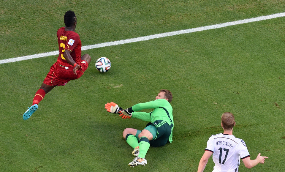 Photo - Ghana's Asamoah Gyan, left, plays the ball past Germany's goalkeeper Manuel Neuer as Germany's Per Mertesacker, right, looks on during the group G World Cup soccer match between Germany and Ghana at the Arena Castelao in Fortaleza, Brazil, Saturday, June 21, 2014. (AP Photo/Francois Xavier Marit, pool)