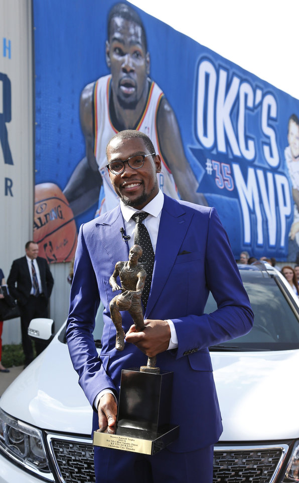 Photo - Oklahoma City Thunder forward Kevin Durant poses for a photo holding the MVP trophy following a news conference announcing him as the winner of the 2013-14 Kia NBA Basketball Most Value Player Award in Oklahoma City, Tuesday, May 6, 2014. Durant spoke at a rally of fans outside the news conference. (AP Photo/Sue Ogrocki)