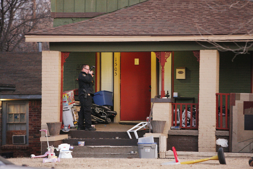 An Oklahoma City police officer takes photos of a shooting scene Friday at a home in the 1500 block of NW 39 in Oklahoma City. Photo by Paul B. Southerland, The Oklahoman <strong>PAUL B. SOUTHERLAND - PAUL B. SOUTHERLAND</strong>