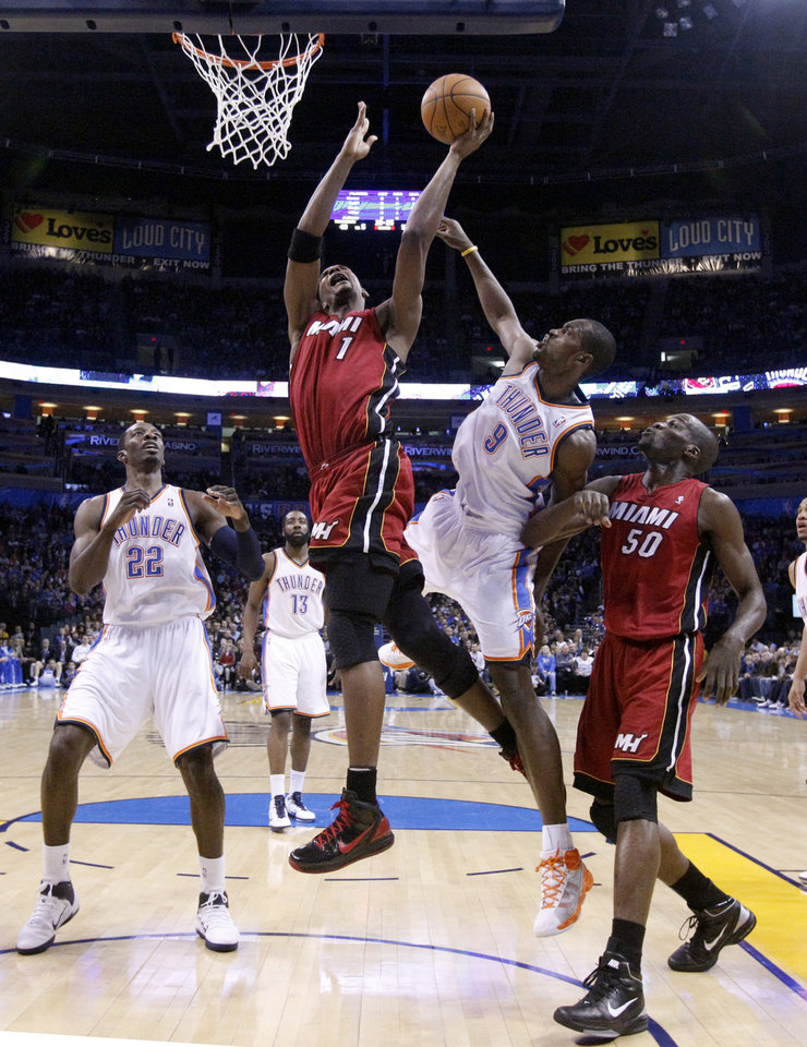 Photo - Miami's Chris Bosh (1) shoots as Oklahoma City's Serge Ibaka (9) defends and Miami's Joel Anthony (50) positions for a rebound during the NBA basketball game between Oklahoma City and Miami at the OKC Arena in Oklahoma City, Thursday, Jan. 30, 2011. Photo by Sarah Phipps, The Oklahoman
