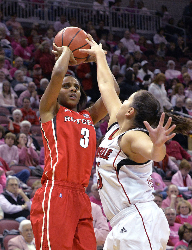 Photo - Rutgers' Tyler Scaife, left, puts up a shot over the defense of Louisville's Shoni Schimmel during the first half of an NCAA college basketball game Sunday, Feb. 23, 2014, in Louisville, Ky. (AP Photo/Timothy D. Easley)