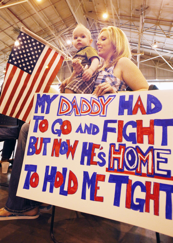 Photo - Shelly Mantooth and 18 month old Collin wait to greet husband and father Spc. Jason Mantooth, as Oklahoma National Guard soldiers return from Afghanistan to a welcome home ceremony in Oklahoma City, OK, Tuesday, March 13, 2012,  By Paul Hellstern, The Oklahoman