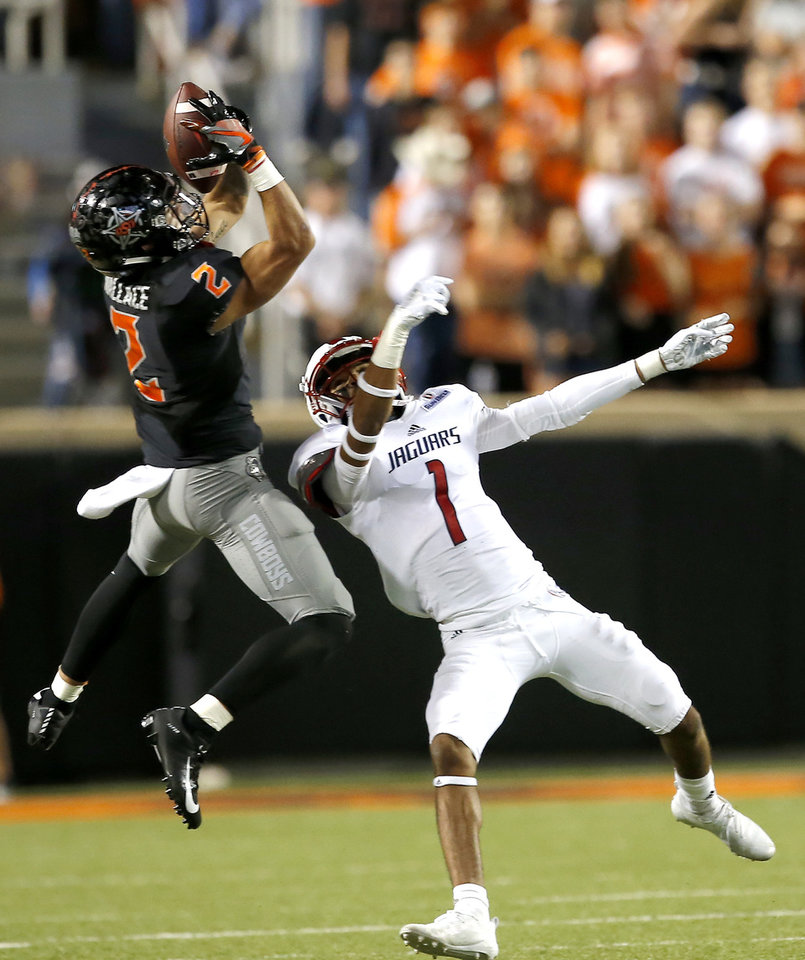Photo - Oklahoma State's Tylan Wallace (2) makes a reception as South Alabama's Jalen Thompson (1) defends in the third quarter during a college football game between Oklahoma State (OSU) and South Alabama at Boone Pickens Stadium in Stillwater, Okla., Saturday, Sept. 8, 2018. Photo by Sarah Phipps, The Oklahoman