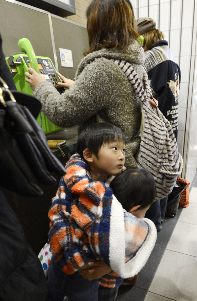 Children cuddle each other while their mother makes a phone call as they are stranded at Sendai railway station in Sendai, Miyagi Prefecture, Friday, Dec. 7, 2012 after trains were halted following a strong earthquake that struck off the coast of northeastern Japan. It is the same region that was hit by a massive earthquake and tsunami last year. (AP Photo/Kyodo News) JAPAN OUT, MANDATORY CREDIT, NO LICENSING IN CHINA, FRANCE, HONG KONG, JAPAN AND SOUTH KOREA