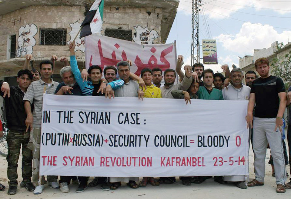 Photo - This photo provided by an anti-Bashar Assad activist group Edlib News Network (ENN), which has been authenticated based on its contents and other AP reporting, show anti-Syrian government protesters carrying a banner and a Syrian revolution flag during a demonstration in Kafr Nabil town, Idlib province, northern Syria, Friday, May 23, 2014. (AP Photo/Edlib News Network ENN)