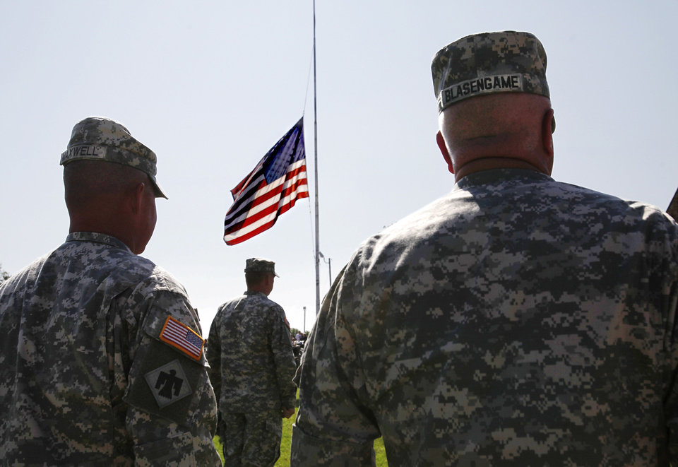Soldiers with the 45th Infantry Brigade stand at attention as the names of those killed during the unit�s recent deployment to Afghanistan are read during a  Memorial Day service in May. OKLAHOMAN ARCHIVE photo
