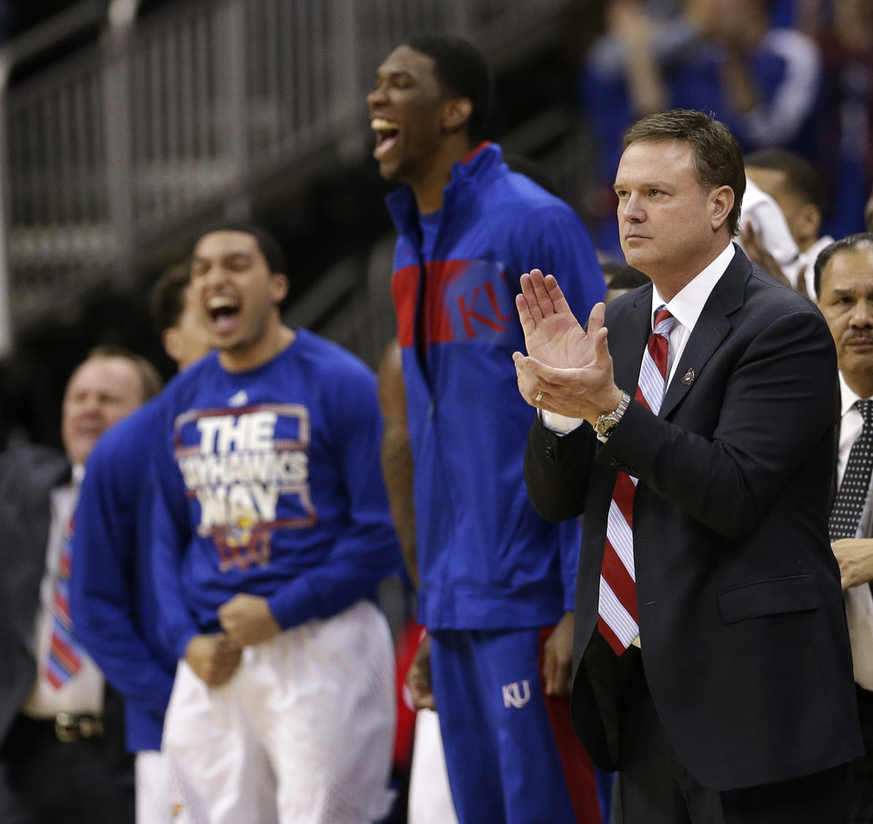 Photo - Kansas coach Bill Self, right, and the Kansas bench celebrate a basket during the first half of an NCAA college basketball game against Iowa State in the Big 12 men's tournament on Friday, March 14, 2014, in Kansas City, Mo. (AP Photo/Charlie Riedel)
