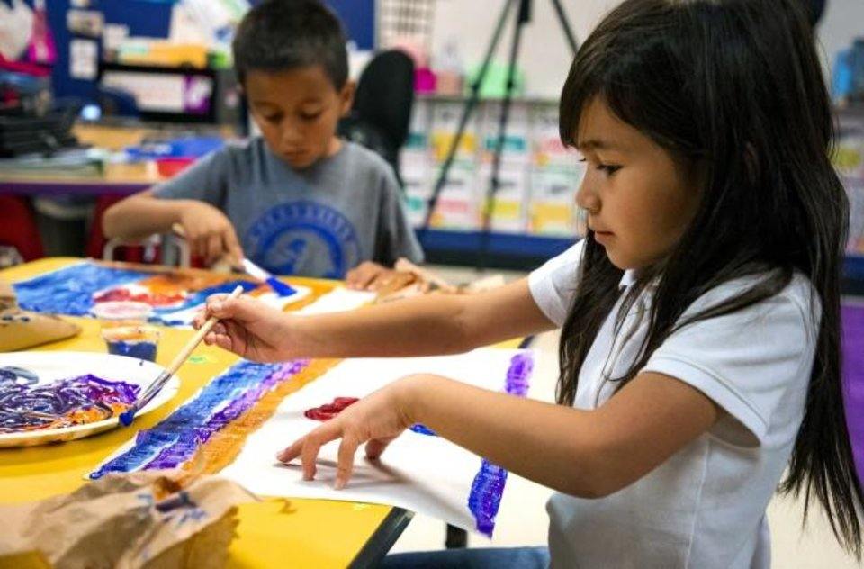 Photo -  Heronville Elementary first grader Jasmine Velasco paints her view of a lesson on the story of Thanksgiving from the Native American perspective while in Alicia Strawn's class at Heronville Elementary in Oklahoma City on Thursday. [Chris Landsberger/The Oklahoman]